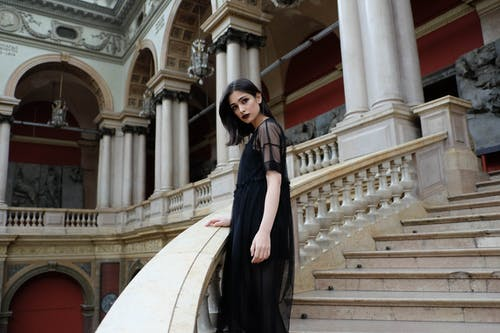 Emotionless woman in black dress standing on majestic marble stairs