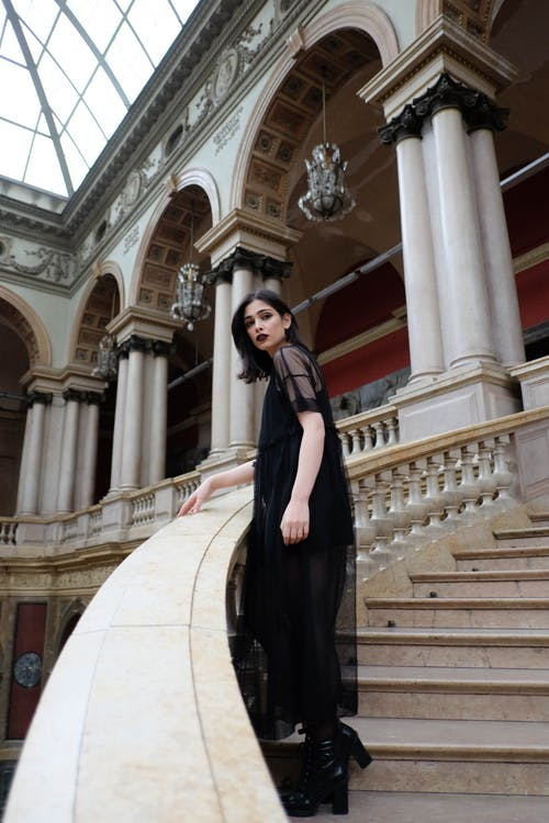 Slim Gothic woman in black dress standing on palace stairs