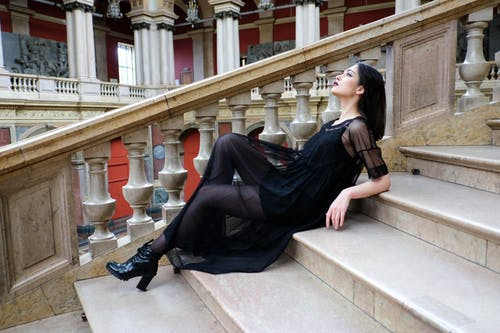 Stylish woman lying on marble stairs in museum