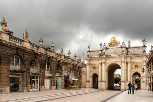 Aged historical Porte Desilles triumphal arch on cloudy day