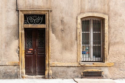 Wooden door and fenced window of aged shabby building located on street in old tow