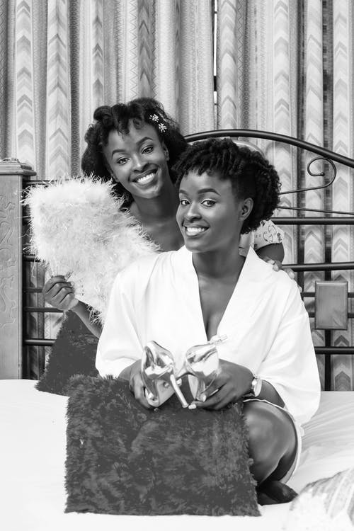 Cheerful black women sitting on bed and smiling at camera