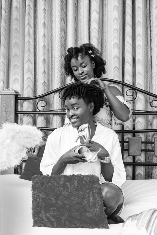 Smiling black friend doing hair of bride before wedding