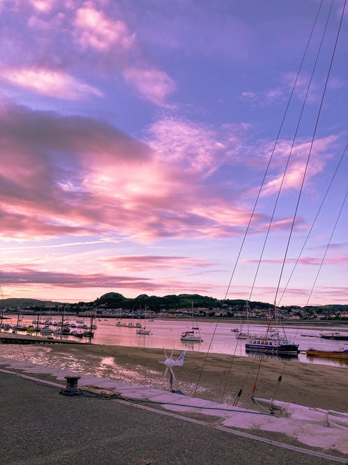 Scenery view of coast with boats floating in water at beautiful pink sunset