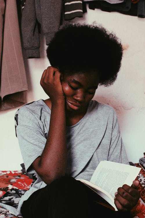 Young African American female with afro hairstyle sitting in room near white wall with hand on cheek while reading book