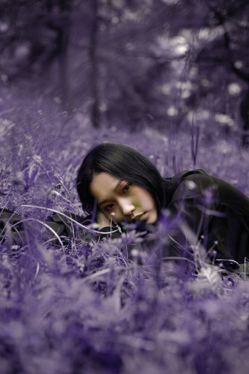 Stylish dreamy ethnic woman among purple flowers