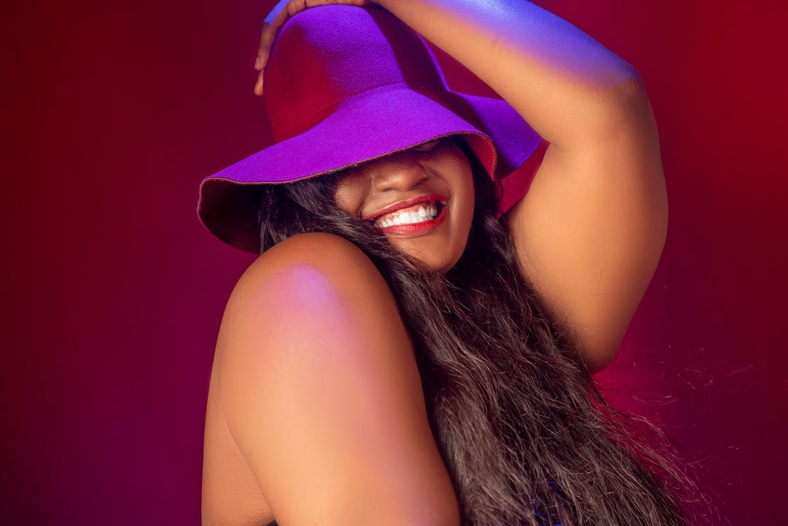 Happy black plump woman in stylish hat smiling brightly