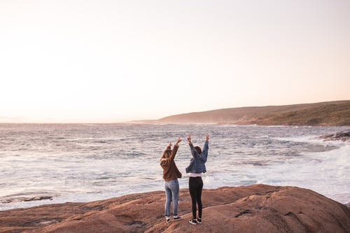 Excited young ladies enjoying sunset over sea with outstretched arms