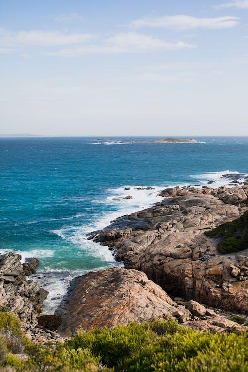 Rocky coast near waving blue ocean in daylight