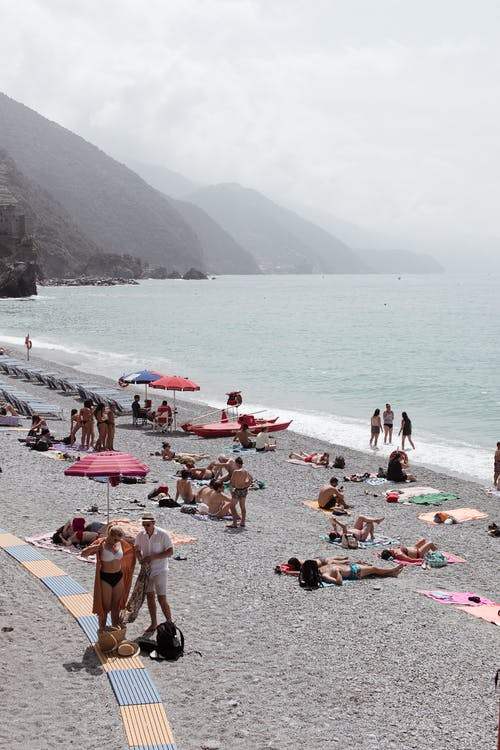 Tourists sunbathing on resort beach near calm sea and mountains covered with green plants in sunny day