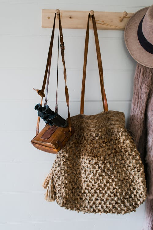 Stylish coat and hat hanging near bag and binoculars on wooden hanger on white wall in apartment