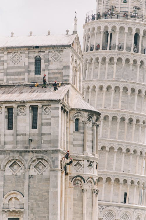 Exterior of famous stone building with ornamental details and leaning tower of Pisa