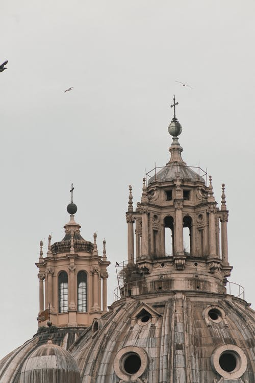 Domes of old famous cathedral decorated with ornamental elements and crosses against overcast sky