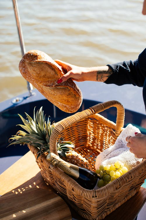 Crop woman with basket of food on yacht