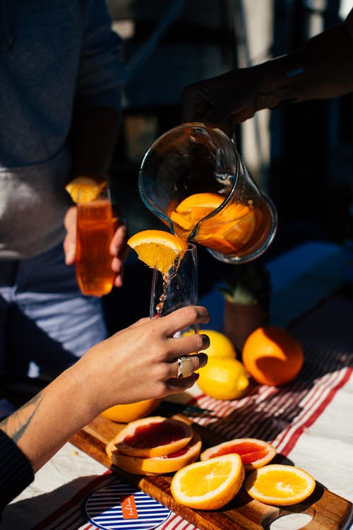 Crop anonymous person pouring fresh cold orange drink from jug into glass during party