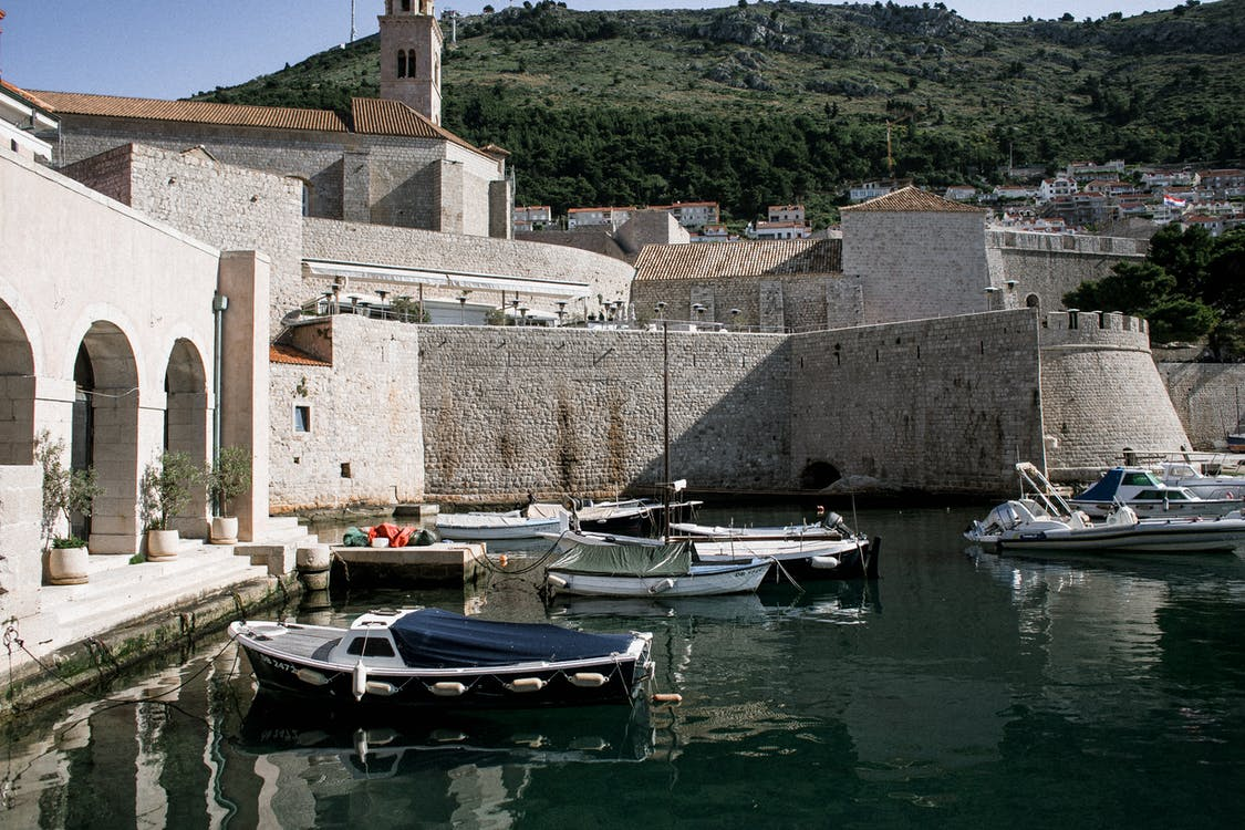 Boats on calm sea water and stone fort