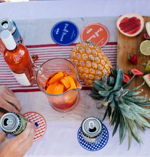 Top view of crop anonymous person placing can of beer on table with drinks and fruits