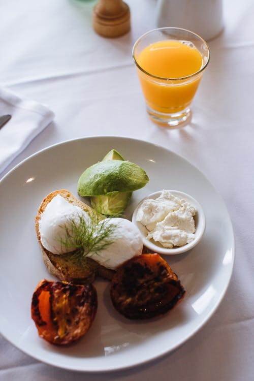 From above of appetizing breakfast with toast and poached eggs served with avocado and glass of orange juice