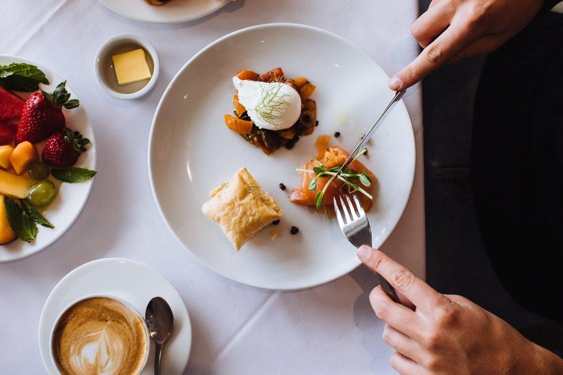 Top view of crop anonymous person having tasty appetizing breakfast with fork and knife having hot aromatic coffee
