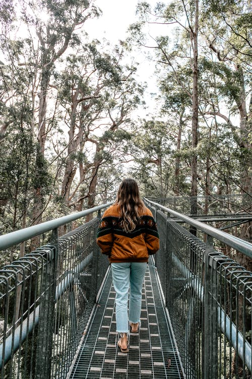 Back view of unrecognizable female in casual clothes strolling on metal footbridge with hands in pockets in park with lush green trees