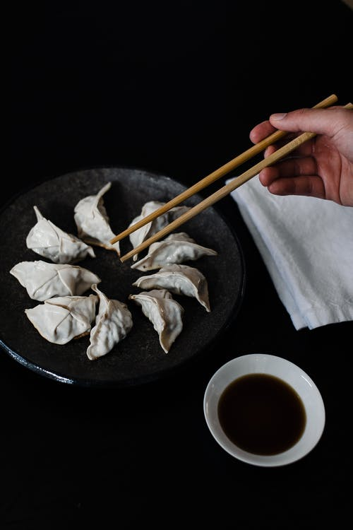 Crop person with chopsticks and gyoza