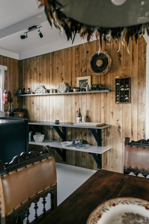Interior of cozy kitchen in country style with shelves and dining zone at home