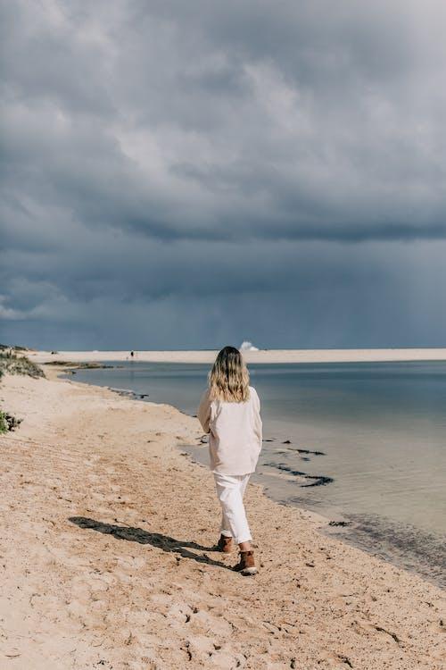 Woman walking along sandy beach