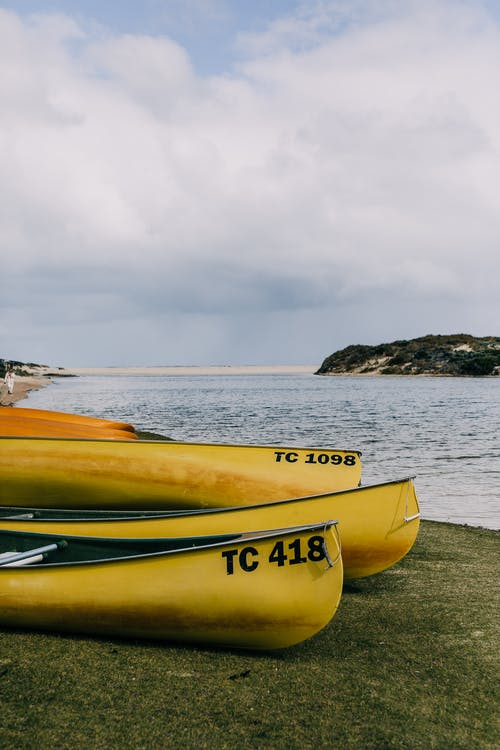 Boats on seashore in cloudy day