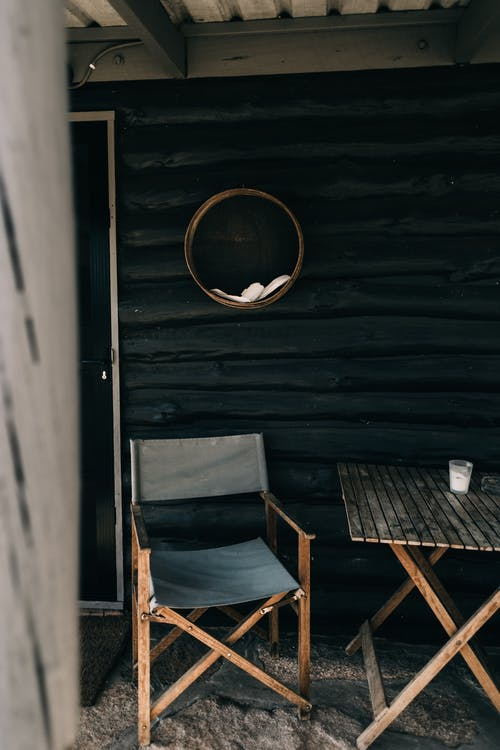 Old outdoor furniture beside wooden house