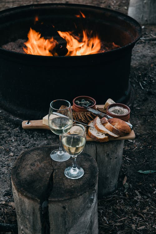 High angle of fire bowl with burning flame and glasses of white wine with snacks on wood stumps