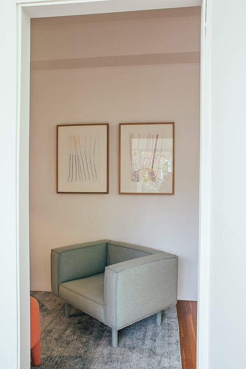 Interior of light room in house with big armchair on carpet and paintings hanging from white wall