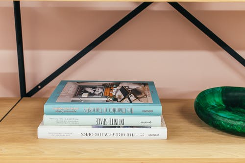 Shelf with books placed near wall