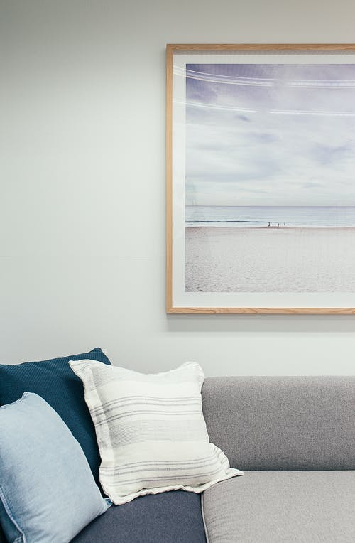 Soft couch with pillows in living room decorated with framed picture of beach and sea hanging on white wall