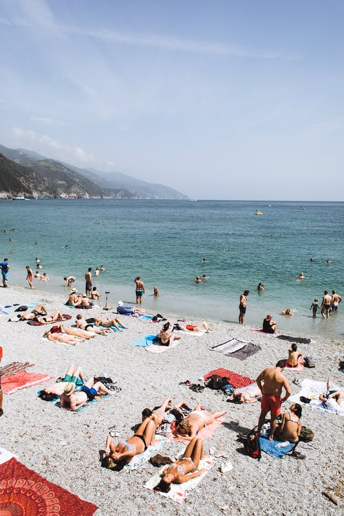 High angle of tourists sunbathing on sandy beach and swimming in rippling turquoise sea water in sunny day