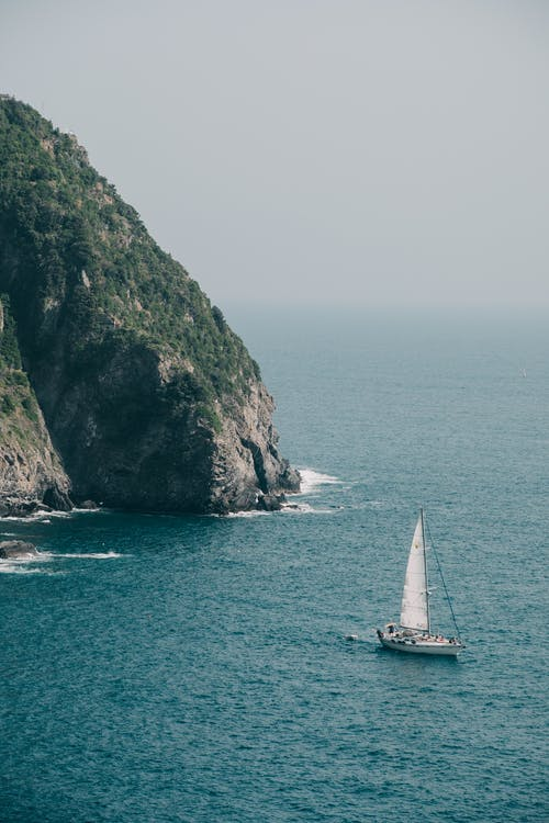 Sailboat floating in sea near rocky cliff