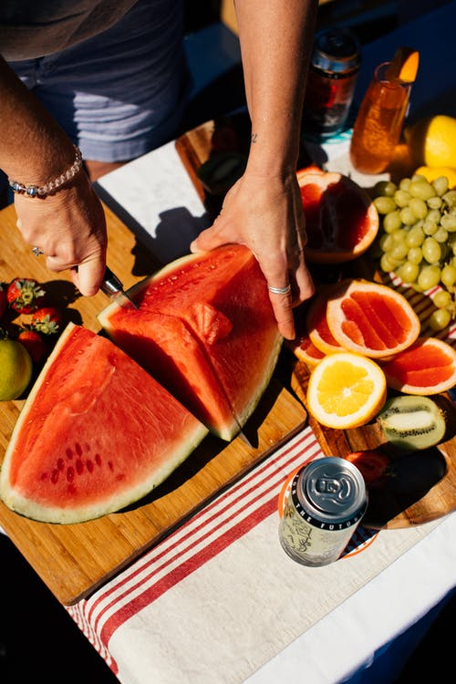 From above crop anonymous female with knife cutting ripe juicy watermelon on table with fruits