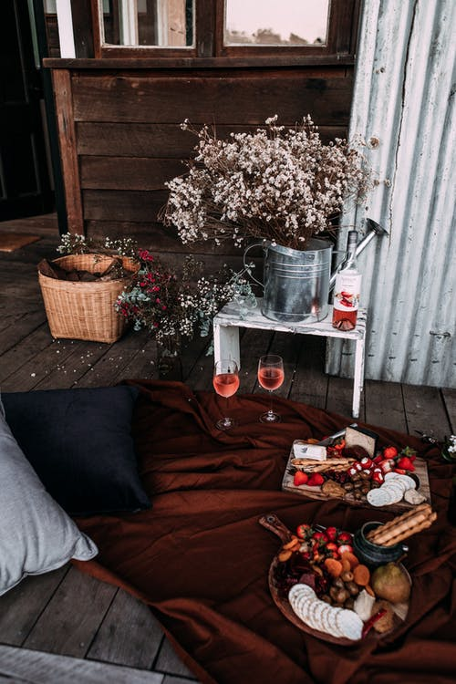 High angle of cozy place prepared for romantic date with wine and snacks on soft plaid