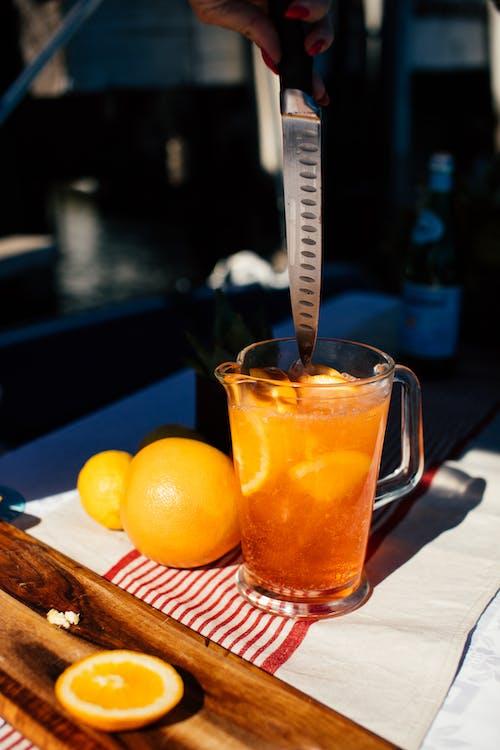 Crop woman stirring drink with orange