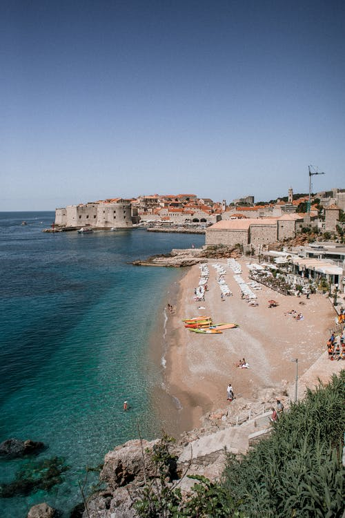 High angle of sandy sea coast with old masonry fortress facade on summer day in Croatia
