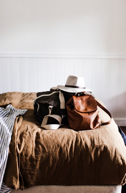 Hat on leather rucksack and travel bag on crumpled bed cover against white wall at home