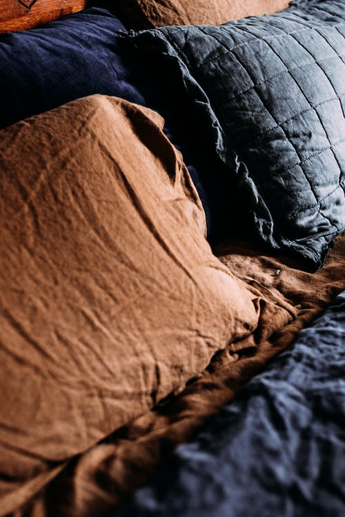 Decorative cushions on crumpled bed sheet at home