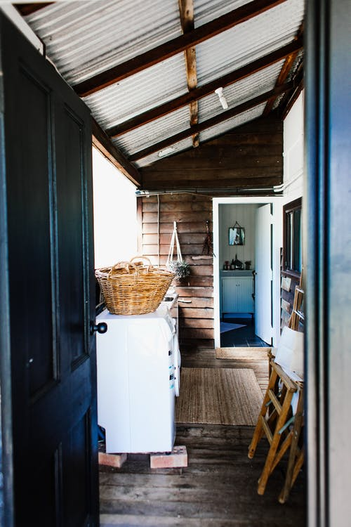 Open door of rustic house with ladder and wicker basket on washing machine in daytime