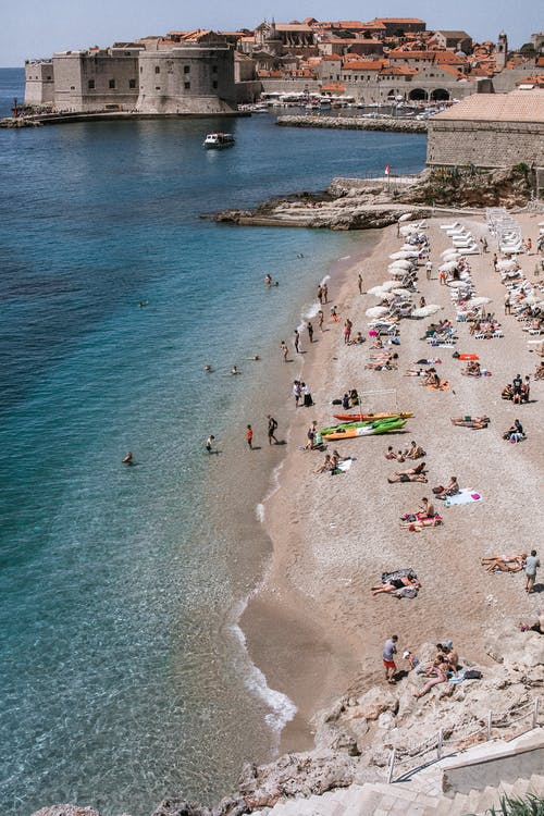 High angle of faceless tourists resting on sandy sea coast against ancient buildings in Dubrovnik Croatia