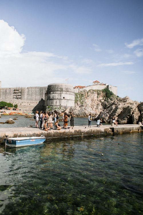 Anonymous tourists on pier in sea against aged fortress