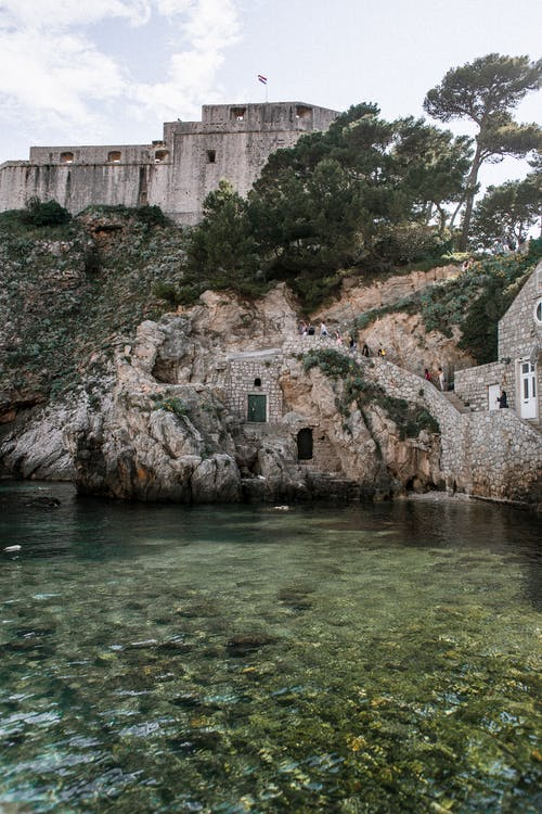 Scenery view of old masonry constructions on mount against Adriatic Sea with pure water in Dubrovnik Croatia