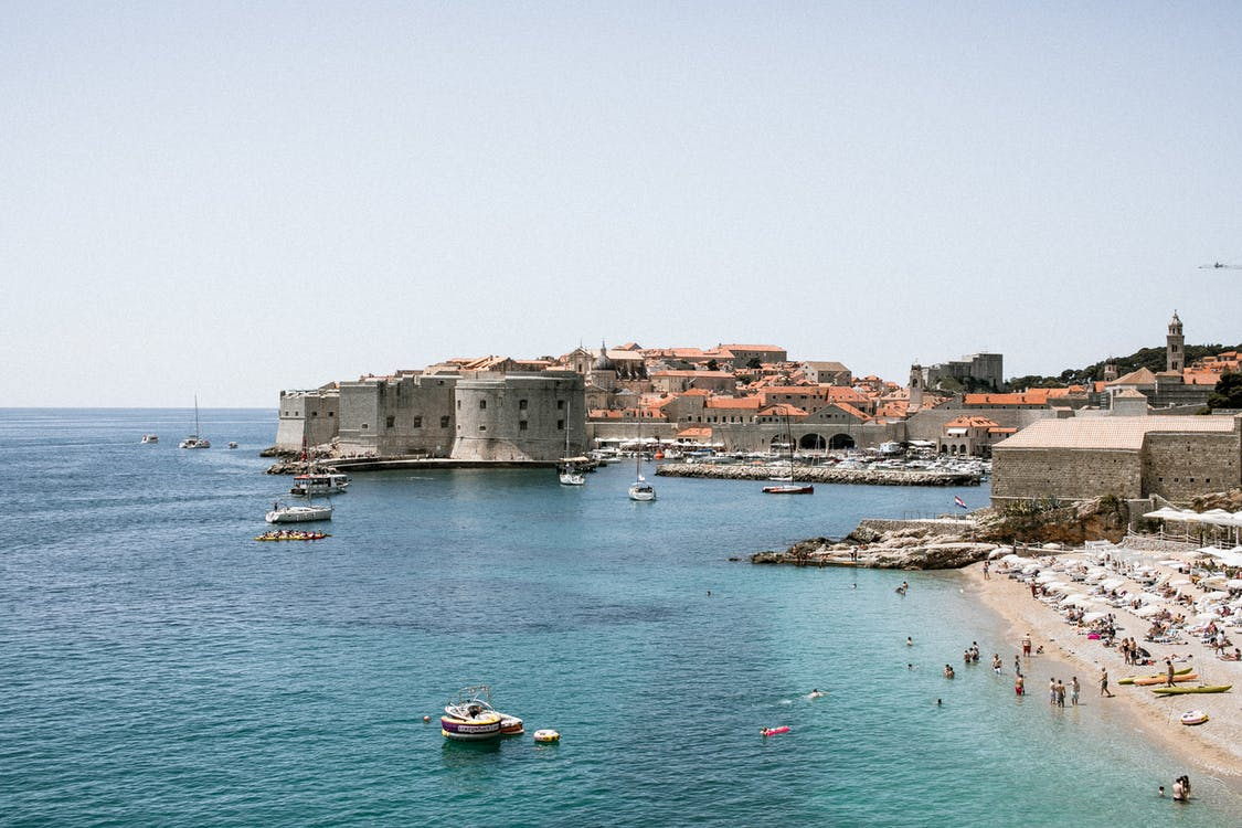Old stone fortress on shore with unrecognizable travelers against sea