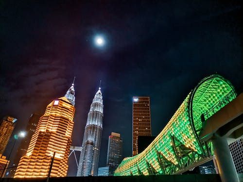 From below exterior of contemporary Petronas Twin Towers located amidst urban city towers and pedestrian overpass illuminated by electrical lights at night