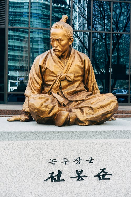 Man in Brown Robe Sitting on Concrete Bench