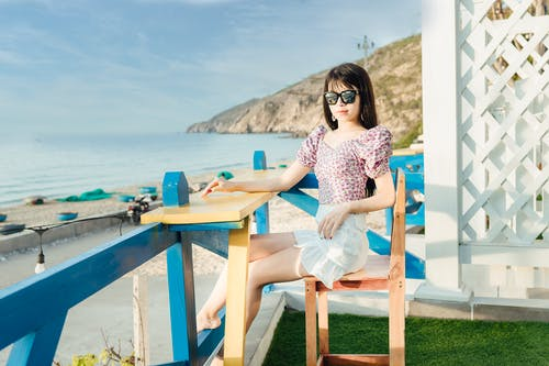 Full body of calm lady in white shorts sitting at wooden counter near blue fence with rippling sea on background