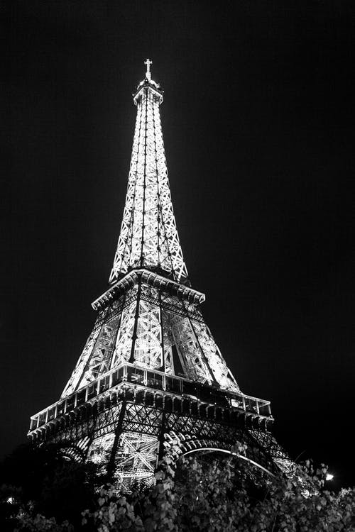 From below of black and white famous Eiffel Tower with glowing lights against dark night sky
